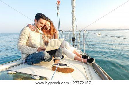 Young Couple In Love On Sail Boat Having Fun Remote Working At Laptop- Happy Luxury Lifestyle On Yac