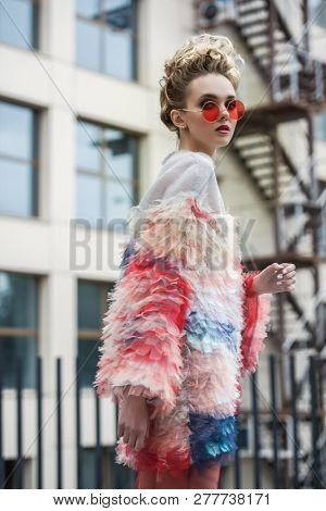 Modern young woman in fluffy dress posing on street outskirts of the city. Beauty, street fashion. poster