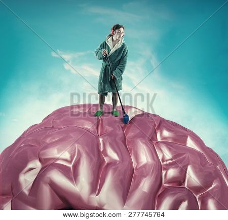 Man Wearing A Gown Cleans A Brain With A Broom. The Concept Of Mental Health.