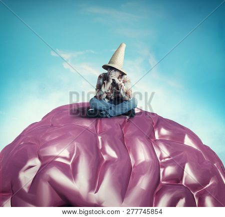 Thoughtful Young Man Sitting On A Human Brain.