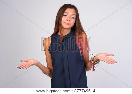 Portrait Of Young Clueless Businesswoman Shrugging Shoulders