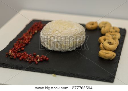 Tomino Cheese On Black Tablecloth Decorated With Small Red Berries And Taralli.