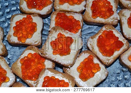 Top View Of Cheap Looking Red Caviar Canape Made With Rye Bread And Butter.
