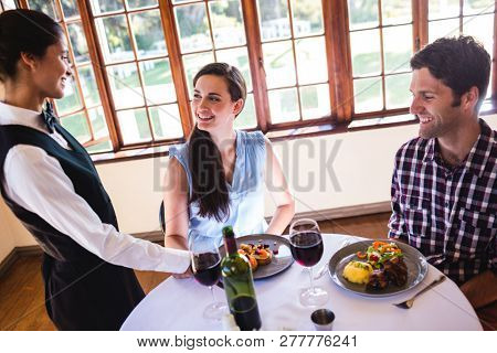 Waitress serving food plate on customers table in restaurant