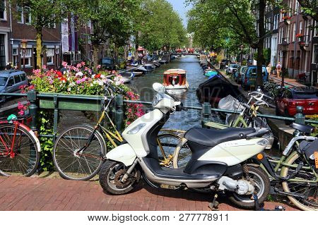 Amsterdam, Netherlands - July 7, 2017: Bicycles And Scooter Parked At Bloemgracht Canal In Amsterdam