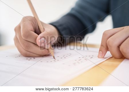 Education Test Exam Concept, High School / University Student Holding Pencil Writing Paper Answer Sh