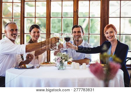 Portrait of business people toasting wine glasses in restaurant