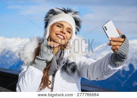 Girl Makes A Selfie In Ski Clothing On Snow Mountain. Stock Photo