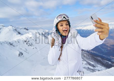 Woman wearing hat make selfie by her phone. Image of young woman wearing hat walking near beach on the street at cold winter day and make selfie by her phone