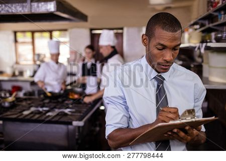 Male manager writing on a clipbaord in kitchen at hotel