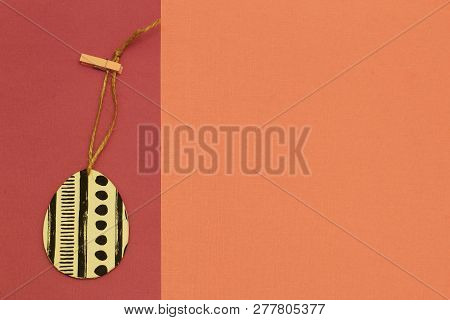 Decorative Exclusive Egg On Jute Cord With A Clothespin On Contrasting Russet And Terracotta Backgro