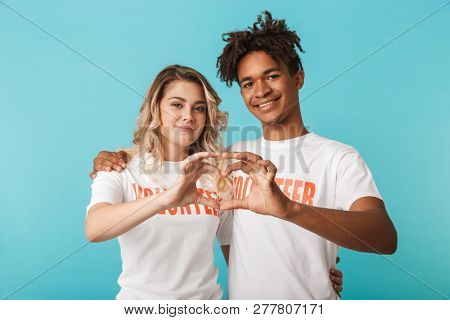 Happy confident multiethnic couple wearing volunteers t-shirt standing isolated over blue background, heart gesture