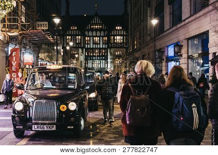 London, Uk - January 05, 2019: People Walking Past Black Cabs Parked On Argyll Street, London, Liber