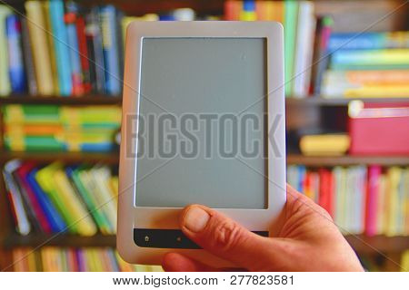 Ebook Or Digital Reading Tablet Device. E-book In Mans Hand. On The Background Is The Shelf With Bri