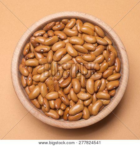 Brown Bean Seeds Are In Wooden Bowl On Beige Background, Legume As Food Ingredient.