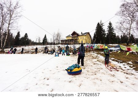 Karpacz, Poland - December 28, 2018: Woman Pulling A Inflatable Sled With Laying Toddler Uphill A Sn