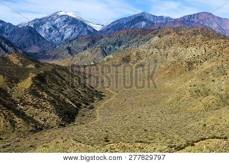 Desert Terrain With Snow Capped Mountains Beyond Taken On An Arid Plain In The Sand To Snow National
