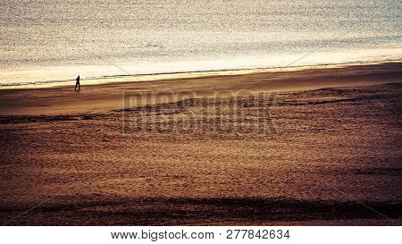 The Silhouette Of A Sunset Runner On The Beach In Coronado, California.