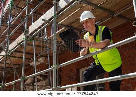 Male builder foreman, construction worker or site manager holding a clipboard, wearing a white hardhat and hi vis vest