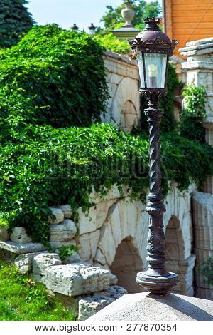 Street Light Lamppost Of Iron Black Color Lantern In Retro Style On The Background Of A Stone Wall O