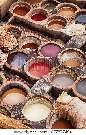 Pits of various colored dyes are used in the Chouara leather tannery in Fes, Morocco, to add color to the leather skins after they have been tanned. poster