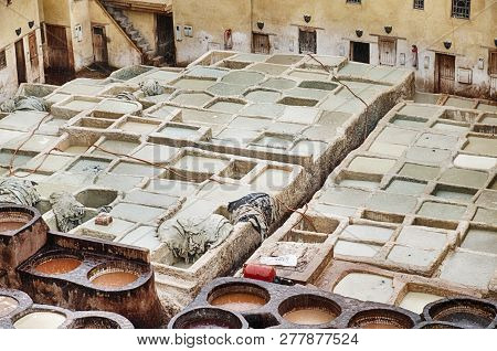 The outdoor leather tannery in Fes in Morocco consists of a number of different pits that are filled with different chemicals to tan and dye leather. poster