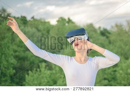 Enjoying New Technology. Pretty Girl In Virtual Reality Headset. Cute Girl Play In Simulated Environ