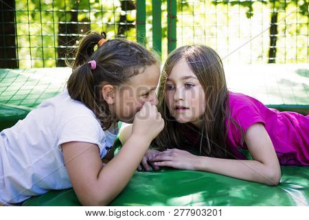 Two Girls Telling A Secret, Lying On The Trampoline, Outdoor In Green Park.