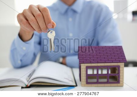 Man in blue shirt hold in hand silver key giving it to buyer closeup. New owner pledge idea for life family solution male arm credit negotiation clerk in office future plan concept poster