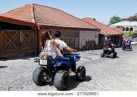 Sighnaghi, Kakheti, Georgia - May 2, 2018: Happy Tourists Riding All Terrain Vehicle On Street Of Th