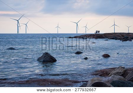 People Watching Wind Mill Power Generator Farm For Renewable Energy Production Along Coast Of Bothni