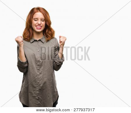 Young beautiful woman over isolated background excited for success with arms raised celebrating victory smiling. Winner concept.
