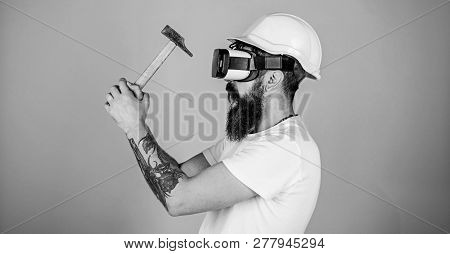 Hipster Busy With Renovation In Virtual Reality. Man With Beard In Vr Glasses Holds Hammer, Light Bl