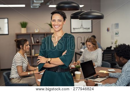 Portrait of sucher colleagues working in background at ofcessful business woman standing with fice. Portrait of cheerful fashion girl in green dress standing with folded arms and looking at camera.
