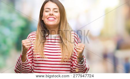 Young beautiful woman casual stripes winter sweater over isolated background excited for success with arms raised celebrating victory smiling. Winner concept.