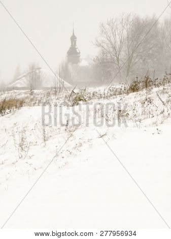Winter Rural Landscape. Snowdrifts Of Snow With Silhouettes Of Old Wooden Rural Buildings On A Hill.