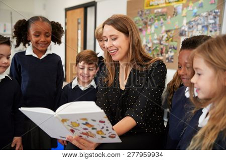 Female primary school teacher reading to a class of school kids standing around her in the classroom, close up