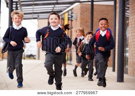 Excited primary school kids, wearing school uniforms and backpacks, running on a walkway outside their school building, front view, close up