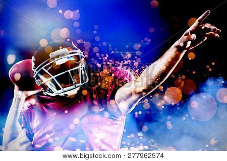 American football player with ball pointing against firework bursting sparkle background
