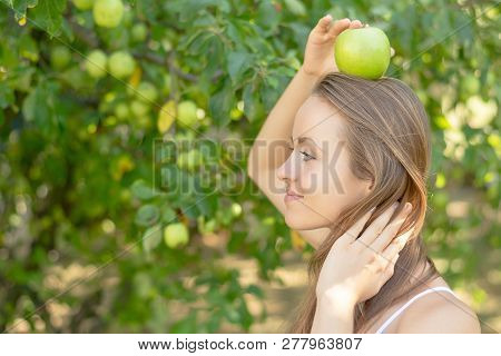 Summertime In Garden. Young Woman Is Holding A Juicy Green Apple In Her Hand.