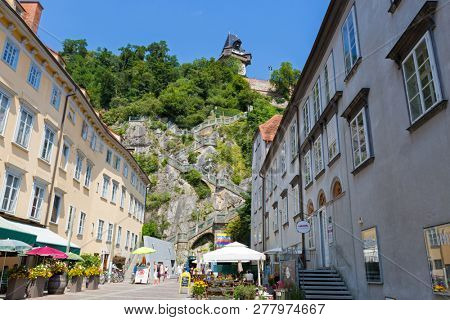 GRAZ, AUSTRIA - JULY 2018 : People walking on Schlossbergplatz with background of staircase going up to Schlossberg Castle Hill in Graz, Austria on July 20, 2018.
