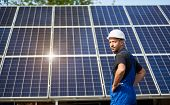 Engineer technician on background of high exterior solar panel photo voltaic system shiny big blue surface. Alternative renewable cheap green energy generation, well done job concept. poster