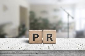 Pr Sign On A Worn Table In A Bright Room With Green Plants And A Microphone