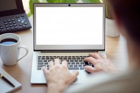 Man with laptop computer on desk working in office with blank screen