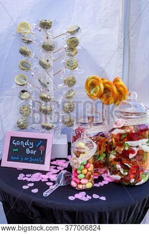 Table With Presentation Of Small Candy Bars With Chocolate Popsicles, Candy Popsicles, Glass Jars Wi