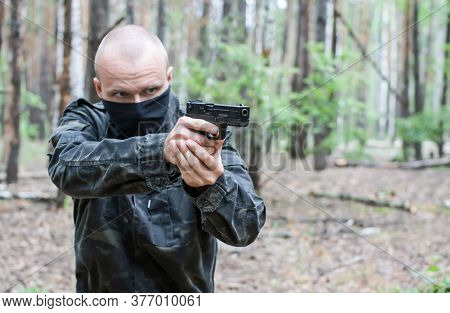 A Man In Dark Military Clothes And A Mask Is Aiming From A Weapon In The Forest, Side View, Close-up