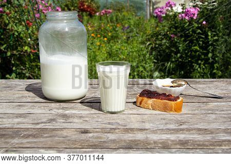 A Faceted Glass Of Milk Stands On A Wooden Table. There Is A Large Two-litre Can Of Milk Nearby. On