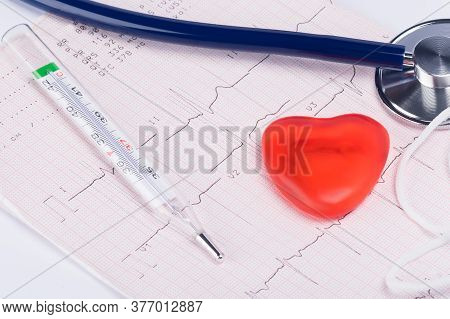 Thermometer For Measuring Body Temperature And A Red Heart, A Concept On A Paper Study Of The Heart