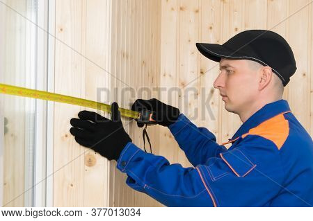 A Man In Construction Clothing Measures The Window Opening With A Tape Measure, Side View, Close-up