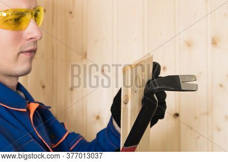 Male Construction Worker In Safety Glasses Pulls A Nail From The Board With A Special Tool